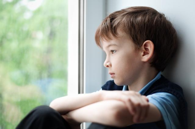 Sad boy, sitting alone, gazing out a window